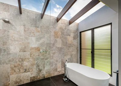 Ensuite with freestanding bath, stone feature wall and glass ceiling open to the sky above