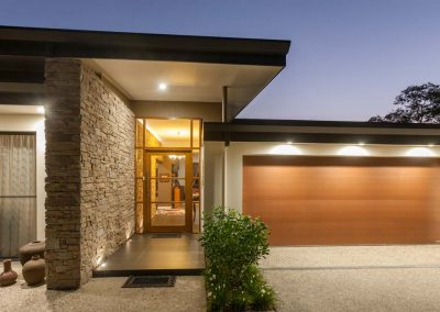 Exterior of front entrance of luxury home with stone feature wall